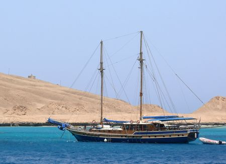 schooner, with masts standing at the pier in the deserted cove with a sandy island photo