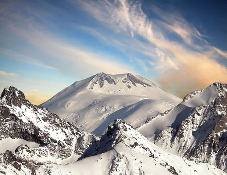 Caucasus Mountains. The top of Mount Elbrus. The reverse side of the mountain. Taken with a mark of 3200 km. Against the backdrop of the sunset sky with clouds.