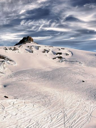 Top of the Caucasus mountain range. Against the background of the sky. Slope with traces of snowboarders and skiers. Deserted winter landscape. photo