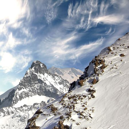 Top of the Caucasus mountain range. Against the background of the sky. On the rugged slopes - snow-covered pine forest.
