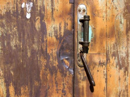 Old rusty door with a worn handle and lock. Stock Photo - 6635945