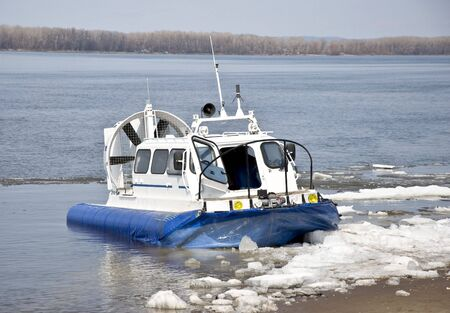 hovercraft: Hovercraft is on the icy shore waiting for passengers to carry across a river.