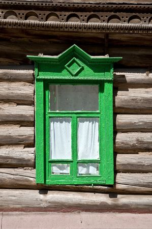 Old window in the log house. Close-up, a fragment of the facade. Russian province. photo