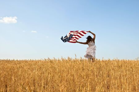 woman blowing: Beautiful young girl holding an American flag in the wind in a field of rye. Summer landscape against the blue sky. Horizontal orientation.