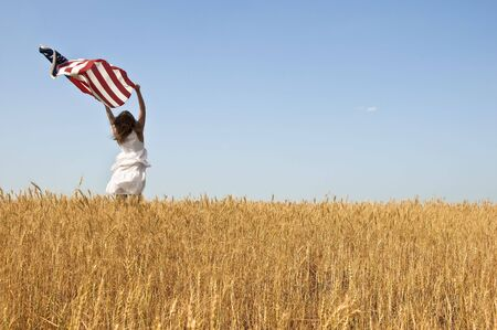 Beautiful young girl holding an American flag in the wind in a field of rye. Summer landscape against the blue sky. Horizontal orientation.