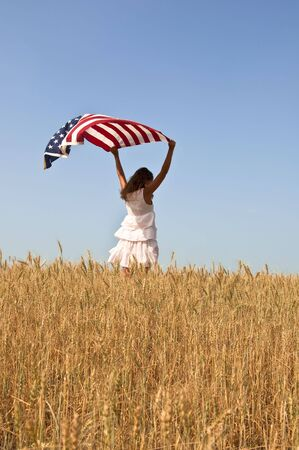 Beautiful young girl holding an American flag in the wind in a field of rye. Summer landscape against the blue sky. Vertical orientation. Zdjęcie Seryjne - 7412866