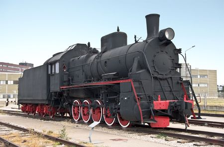 Steam locomotive beside a railway station platform. Retro train. photo