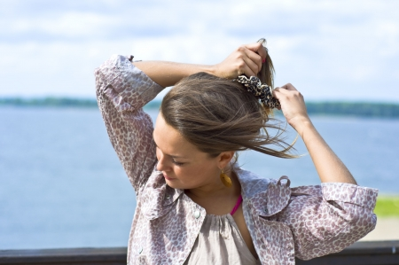 Young beautiful girl tying her hair hairpins. Summer portrait. Blurred background.