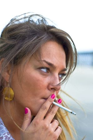 Young beautiful girl smokes. Purple manicure. Summer portrait on the beach. Blured focus.
