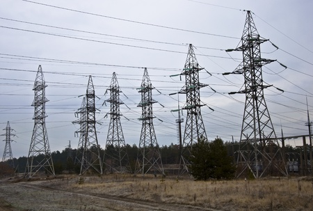 Power transmission towers in the autumn forest. Overcast sky. Stock Photo
