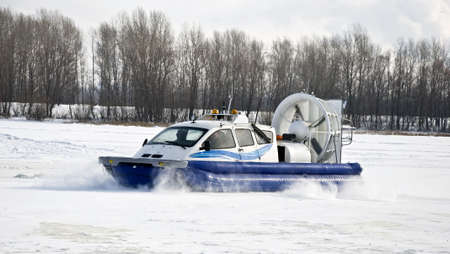 hovercraft: Hovercraft rides on the frozen river, picking up snow dust. Winter
