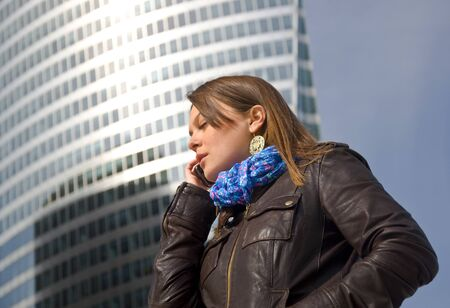 Beautiful business woman talking on a cell phone against a glass skyscraper. Stock Photo - 9452092