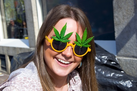 Beautiful young girl smiling in sunglasses in the form of cannabis. Amsterdam.