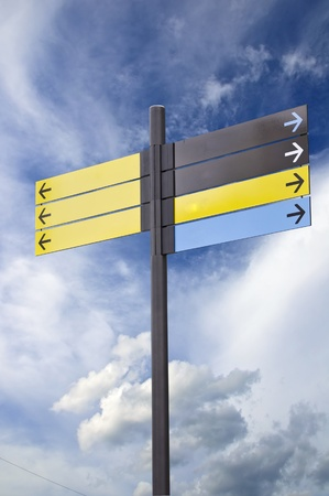 informational: Colorful plastic informational signs with arrows. Show the direction. Against the blue sky with clouds