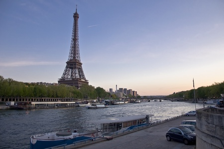 Eiffel Tower on the banks of the River Seine at sunset. Urban night landscape. Stock Photo