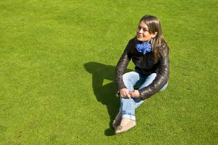 Attractive girl sitting on a green lawn. Spring. photo