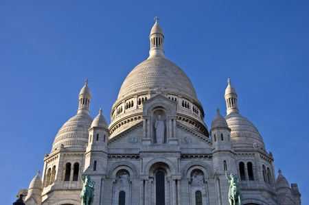 Basilica of Sacre Coeur in Paris. Against the blue clear sky. Urban scene.