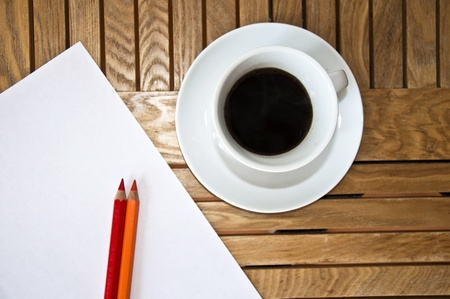 Paper blank Sheet, color pencil and a cup of coffee on a wooden table. photo
