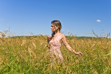 Beautiful young woman in a field of rye. Touch the ears harvest by hand. Rural landscape.