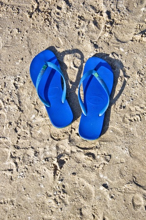 Blue summer shoes on the beach. Flip-flops on the sand. photo