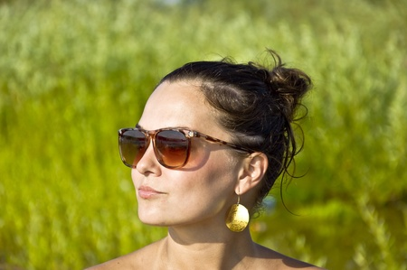 Beautiful young girl in sunglasses on the beach. Portrait. Blurred background. Summer portrait.