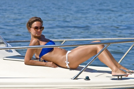 Beautiful woman sunbathing on the deck of the yacht. Summer portrait on the river photo