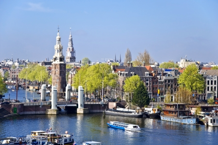 Classical Amsterdam view. Boat floats on the channel on the background of bridge. Urban scene.