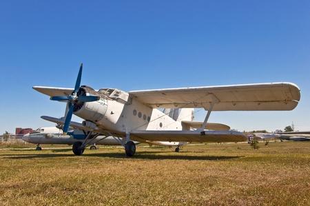 old russian airplane on grass and blue sky background Zdjęcie Seryjne