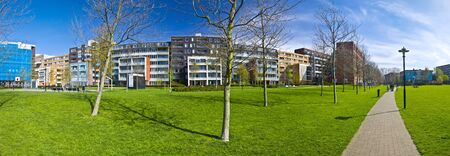 arhitecture: modern residential area of Amsterdam. Park with green grass and trees on the background of modern arhitecture. XXL size. Panorama