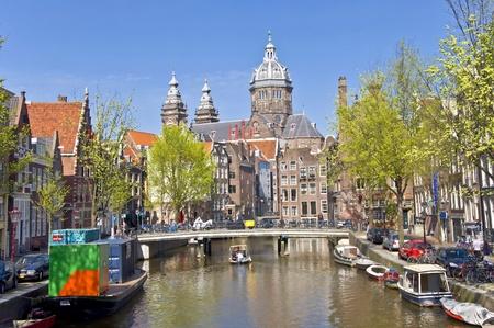 house gables: La vista cl�sica de Amsterdam. Vista desde el canal de la iglesia contra el cielo azul. Paisaje urbano de Amsterdam. Editorial