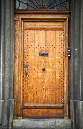 Old wooden door in the town of Mons. Belgium. Fragment, close-up. photo