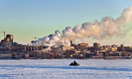 evaporacion: Paseos en motos de nieve sobre el río congelado en el fondo de la ciudad con el paisaje industrial. Puesta de sol. Samara. Rusia. Foto de archivo