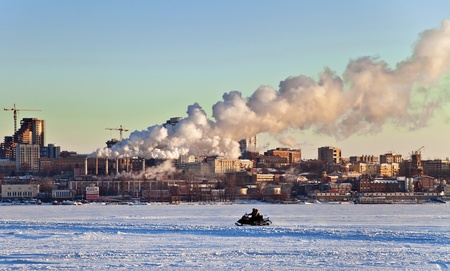 Snowmobile rides on the frozen river in the background of the city with the industrial landscape. Sunset. Samara. Russia.