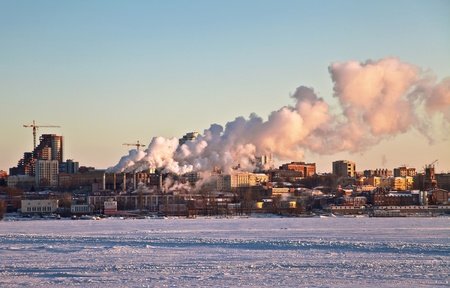 Heat Thermal station is on the shore of the frozen of the river in Samara. Against the backdrop of the sunset light and the sky. Out of the smoke pipe is. Samara. Russia. Zdjęcie Seryjne