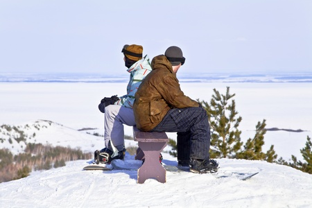 Two snowboarders resting on top of mountain against the backdrop of a beautiful winter landscape  Back to back  photo