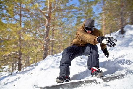 offpiste: Snowboarder rides at high speed through the winter forest. Close-up. Motion Blur.
