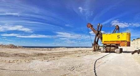 Heavy excavator in quarry for the extraction of gravel  Against the background of blue sky  Stock Photo