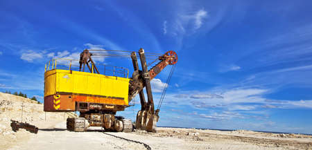 erosion: Heavy excavator in quarry for the extraction of gravel  Against the background of blue sky  Stock Photo