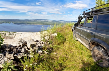 All-wheel drive SUV on the edge of a cliff in a quarry rubble  Against the background of blue sky
