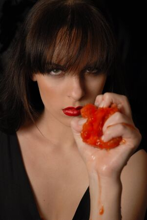 threateningly: The beautiful girl threateningly looks, has crushed a tomato in a hand
