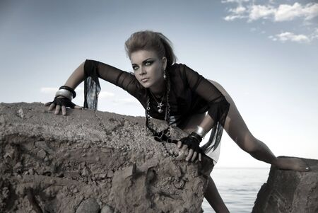 audacious: rock girl on a concrete slab in an interesting position