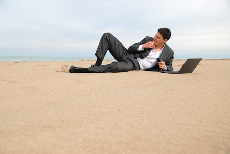 untruth: A young businessman lying on the beach in front of a laptop, he thought.