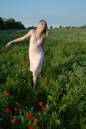 Young blond girl in a pink sarafan walking in a field where poppies bloom photo