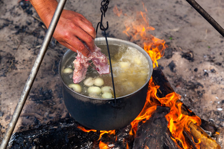 fish fire: fish soup cooking in a pot on a fire in the forest by the sea Stock Photo
