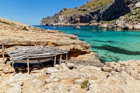turquoise water: The boat rests under the wooden shed near the picturesque beach,Shed for a boat