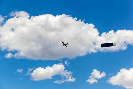 The plane flies in the sky among the clouds with an advertising sign,Advertising in the sky Stock Photo