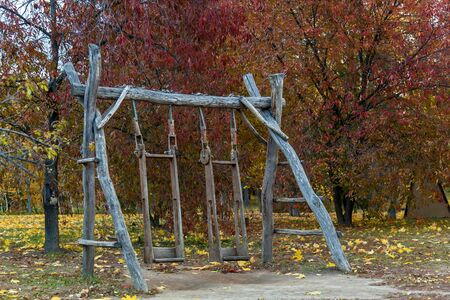 Old, as if home-made wooden swing at the park against the autumn trees and fallen leaves Stock Photo