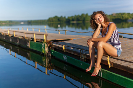Beautiful girl on the shore.Young girl with curly hair, denim shorts and striped t-shirt sits on pier at the river bank. Stock Photo