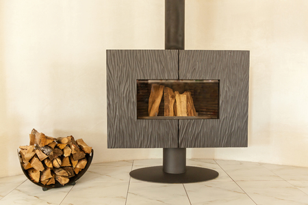 cast in place: Wood stove-fireplace. Modern wood stove-fireplace is bolted to the floor, with a long tube and wood inside