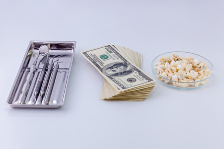 doctor money: Dental instruments for teeth.Dental instruments in the silver dish, pack of dollars and teeth in glass plate on a white background.